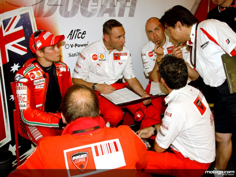Casey Stoner with Ducati staff in garage
