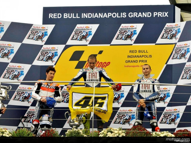 Rossi with his flag on the podium with Hayden and Lorenzo at Indianapolis