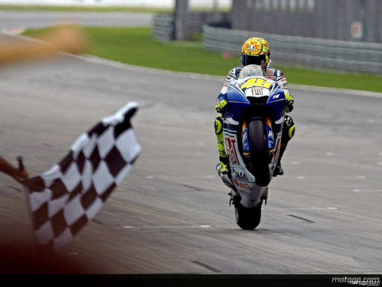 Valentino Rossi pulls off a wheelie at the finish of the race