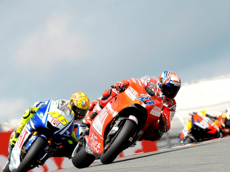 Casey Stoner riding ahead of Valentino Rossi in Sachsenring
