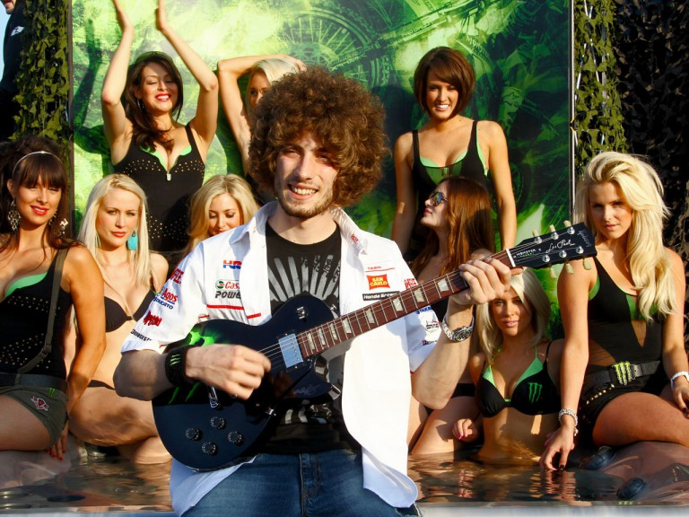Simoncelli plays the guitar to paddock girls at the Monster Energy BBQ