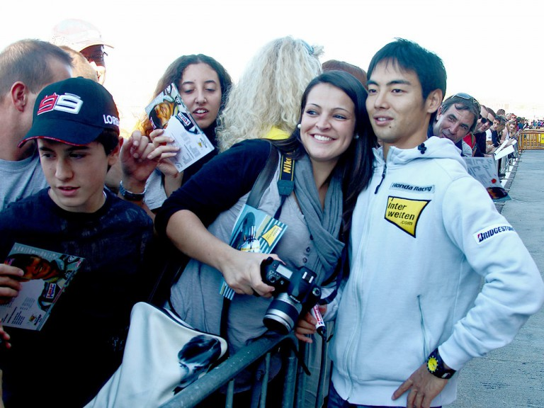 Hiroshi Aoyama attending fans at the paddock in Valencia