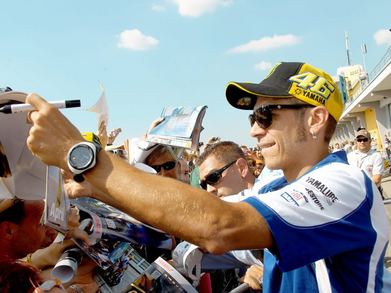 Valentino Rossi attending fans at the paddock in Sachsenring