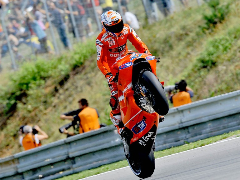 Casey Stoner pulls off a wheelie during QP in Brno